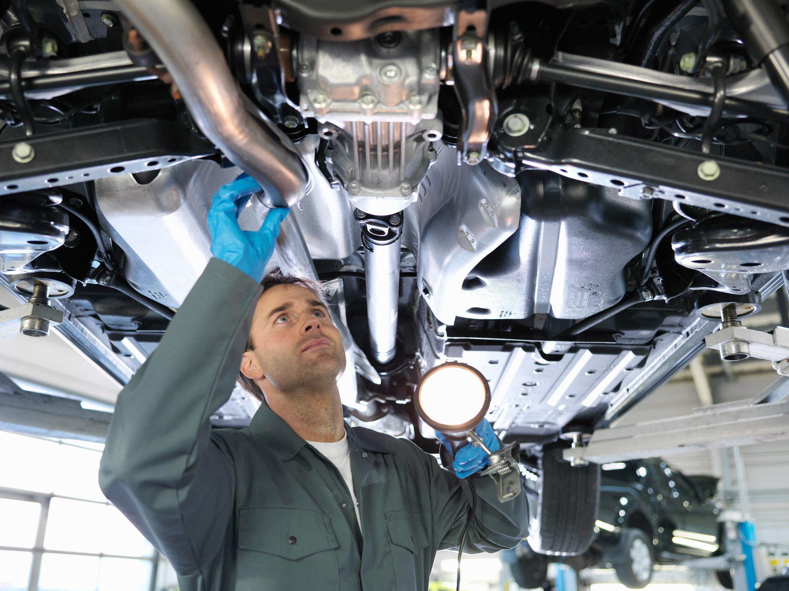 Mechanic working under car --- Image by © Monty Rakusen/cultura/Corbis