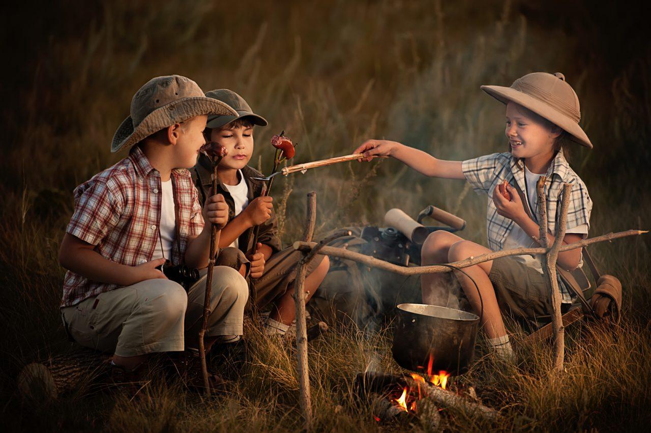 Group of children sitting around the campfire travelers